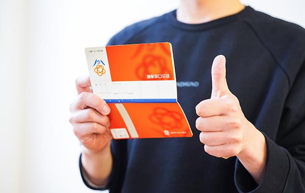 写真:通帳を持つ男性